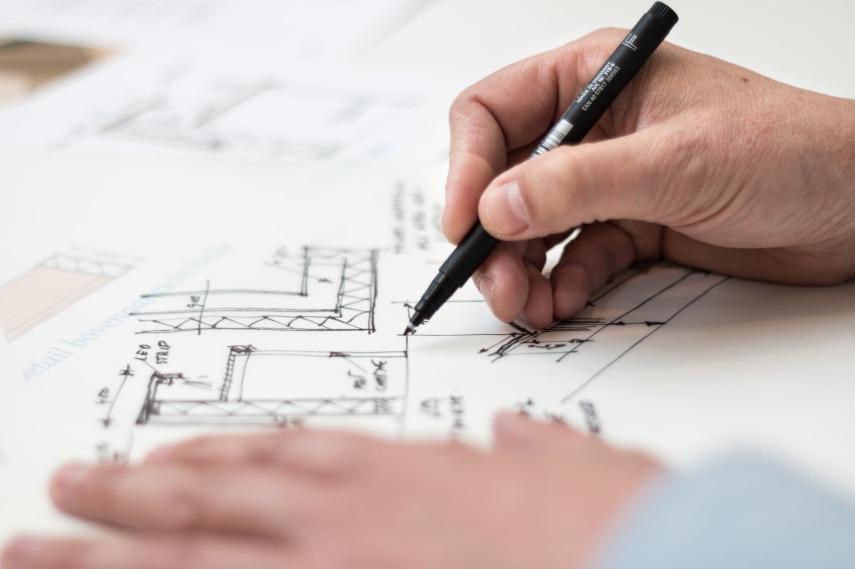 Męskie ręce trzymające rysik i szkicujące wewnętrzny plan domu lub mieszkania