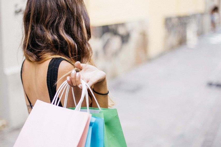 Widziane od tyłu kobieta o ciemnych włosach z naręczem papierowych toreb zakupowych