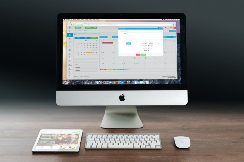 Na drewnianym biurku stoi biały zestaw komputerowy Apple'a: monitor, klawiatura, myszka