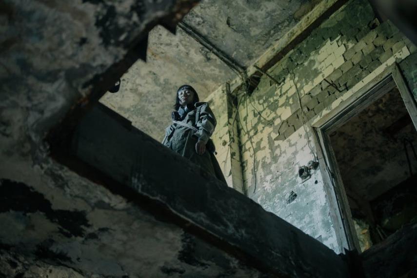 Przerażająca kobieta patrząca z góry w długie sukni stoi w ruinach